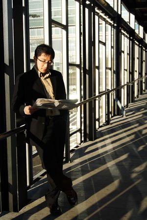 estacion de tren: Un empresario leer un peri�dico en una estaci�n de tren