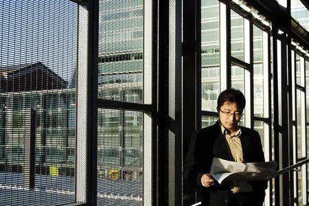 estacion de tren: Un hombre de negocios que lee el peri�dico financiero en una estaci�n de tren