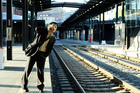 A businessman talking on the phone while waiting for the train  photo