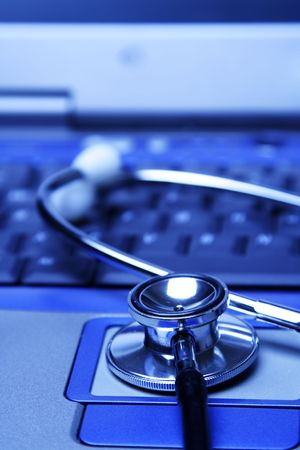 A stethoscope and a laptop in a blue tone