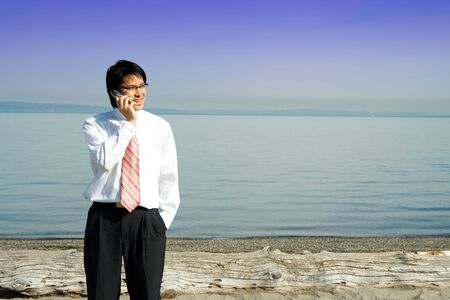 teleconference: A businessman talking on the cell phone at the beach