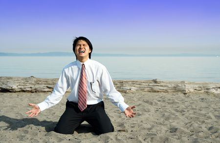 man kneeling: A stressed and frustrated businessman screaming on the beach Stock Photo