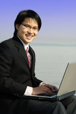 A businessman working on his laptop at the beach photo