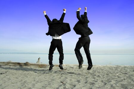 Two businessmen jumping and celebrating on the beach photo