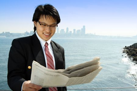 A businessman reading a financial newspaper on the beach Stock Photo