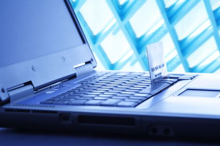 technology transaction: A shot of a laptop and a credit card in a blue tone, can be used as e-commerce concept Stock Photo