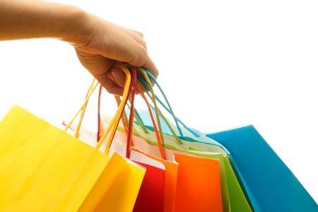 Una mujer llevando la mano un ramo de coloridas bolsas de la compra  Foto de archivo