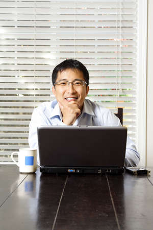 An asian businessman working on his laptop  photo