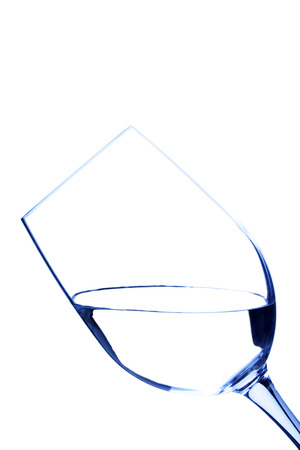 A shot of a wine glass containing water in blue tone