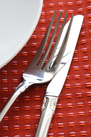 A shot of a dining table with plate, fork and knife on a red tablecloth