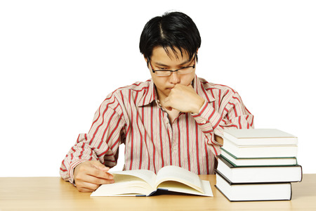 scholarly: An isolated shot of a young man reading books Stock Photo