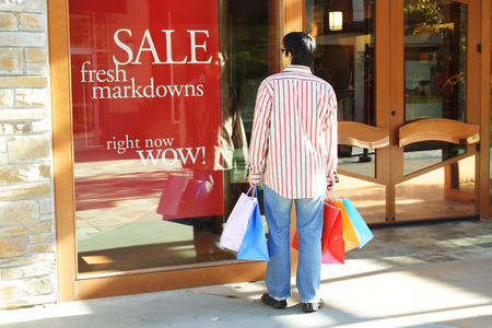 sales person: A young man carrying shopping bags looking at sale sign at an outdoor shopping mall