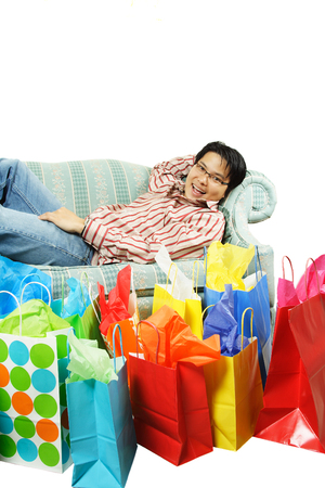 A happy young man lying on a sofa after shopping Banco de Imagens
