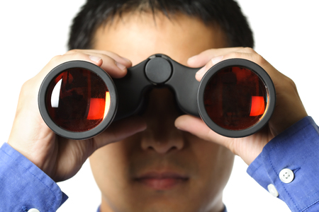 predicting: An isolated shot of a businessman looking through a binocular Stock Photo