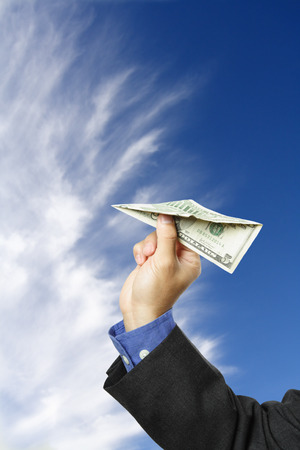 A businessman trying to fly a paper airplane made out of dollar bill, can be used as money concept photo