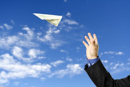 flying man: A businessman trying to fly a paper airplane made out of dollar bill, can be used for money concept Stock Photo