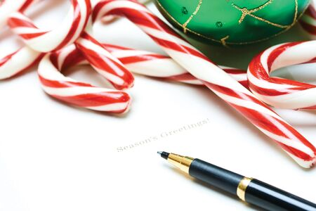 A shot of a christmas greeting card with candy canes and christmas ornament