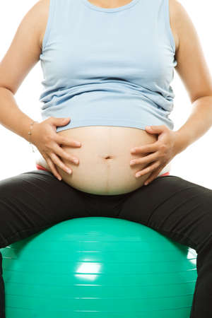 An isolated shot of a pregnant woman exercising with a birth ball Stock Photo - 1703377