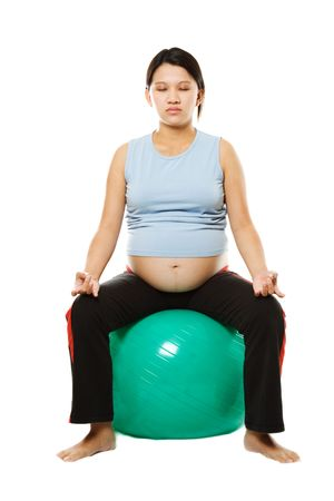 A pregnant woman mediitating on an exercise ball Stock Photo - 1737187