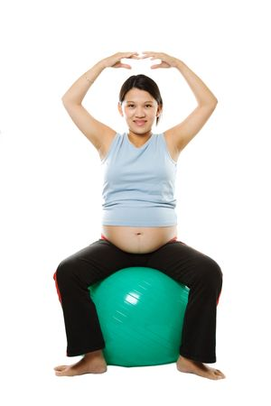 A pregnant woman exercising with an exercise ball photo