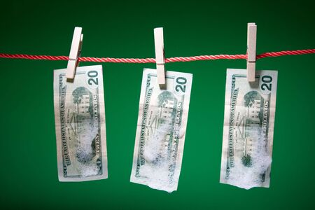 A shot of dollar bills washed with soap hanging on clothesline photo