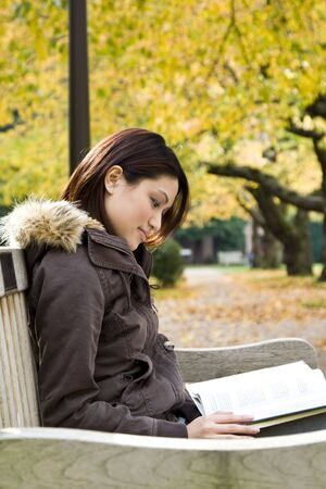 A pretty college student studying on a bench in campus  photo