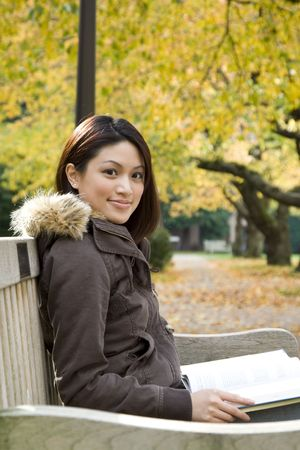 A beautiful college student reading on the bench at the campus Stock Photo - 2048039