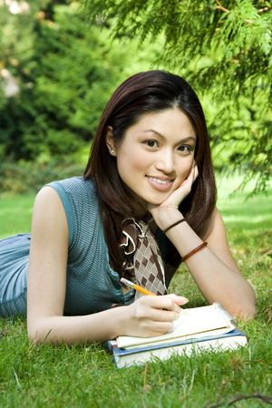 A beautiful college student studying outdoor in the park photo
