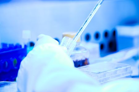A scientist working on a DNA sample test at the lab (shot in blue tone)