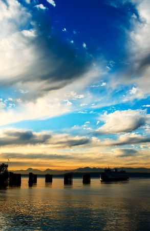 edmonds: A beautiful scenery of a ferry coming into a dock against the Olympic Mountains during the sunset Stock Photo