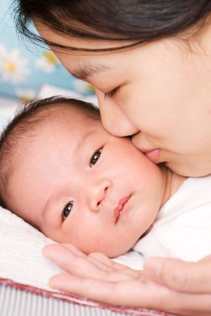 An asian mother kissing her baby boy Stock Photo