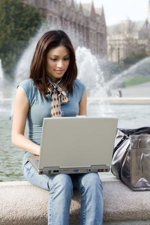 A portrait of a beautiful young woman working on her laptop outdoor photo