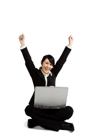 A happy and successful businesswoman with her arms raised working with a laptop photo