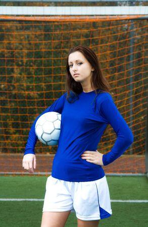 A beautiful soccer player carrying a soccer ball Banco de Imagens