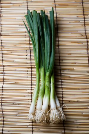 asian produce: A shot of spring onions or scallions on a bamboo mat Stock Photo
