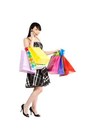 A beautiful woman carrying shopping bags while talking on the phone photo