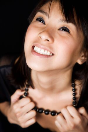 A portrait of a happy beautiful young asian woman pulling on her necklace, can be used as freedom concept Stock Photo - 2586487