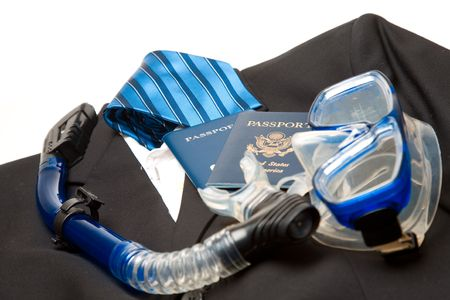 A shot of a suit and tie and passports and snorkeling equipment, can be used for business travel concept photo