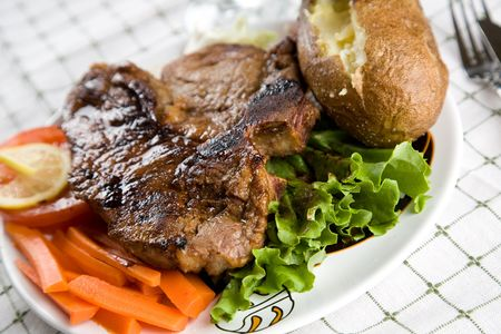 A juicy t-bone steak with baked potato and vegetables
