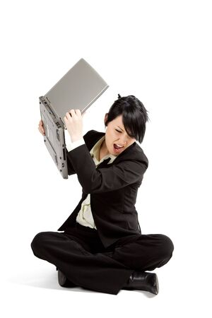 An angry and stressed businesswoman throwing away her laptop photo