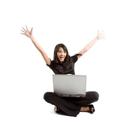 working woman: A happy woman raising her arms while working on her laptop Stock Photo
