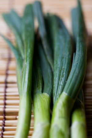 scallions: A shot of spring onions or scallions on a bamboo mat Stock Photo