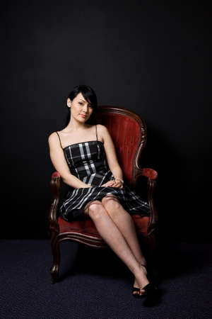 antique chair: A fashion shoot of a beautiful woman sitting on a vintage chair Stock Photo