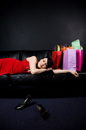 A shot of a beautiful woman resting on a sofa after a shopping trip photo