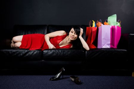 A shot of a beautiful woman resting on the sofa after shopping photo