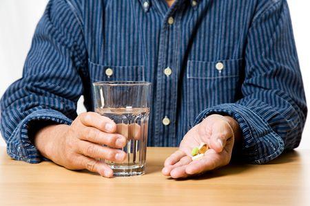personas tomando agua: Una foto de un hombre de categor�a superior de tomar el medicamento con un vaso de agua  Foto de archivo
