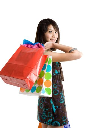 An isolated shot of a beautiful asian girl carrying shopping bags Stock Photo