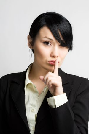 A businesswoman with her fingers on her lips photo