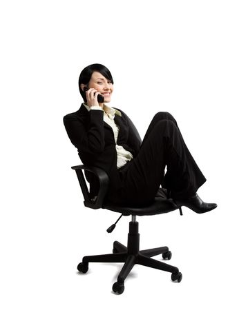 An isolated shot of a businesswoman sitting on a chair and talking on the phone photo