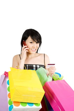 A woman carrying shopping bags calling credit card company photo